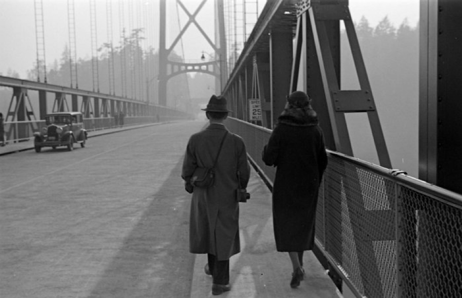 A woman and man walking across the Lions Gate Bridge, a year before it opened